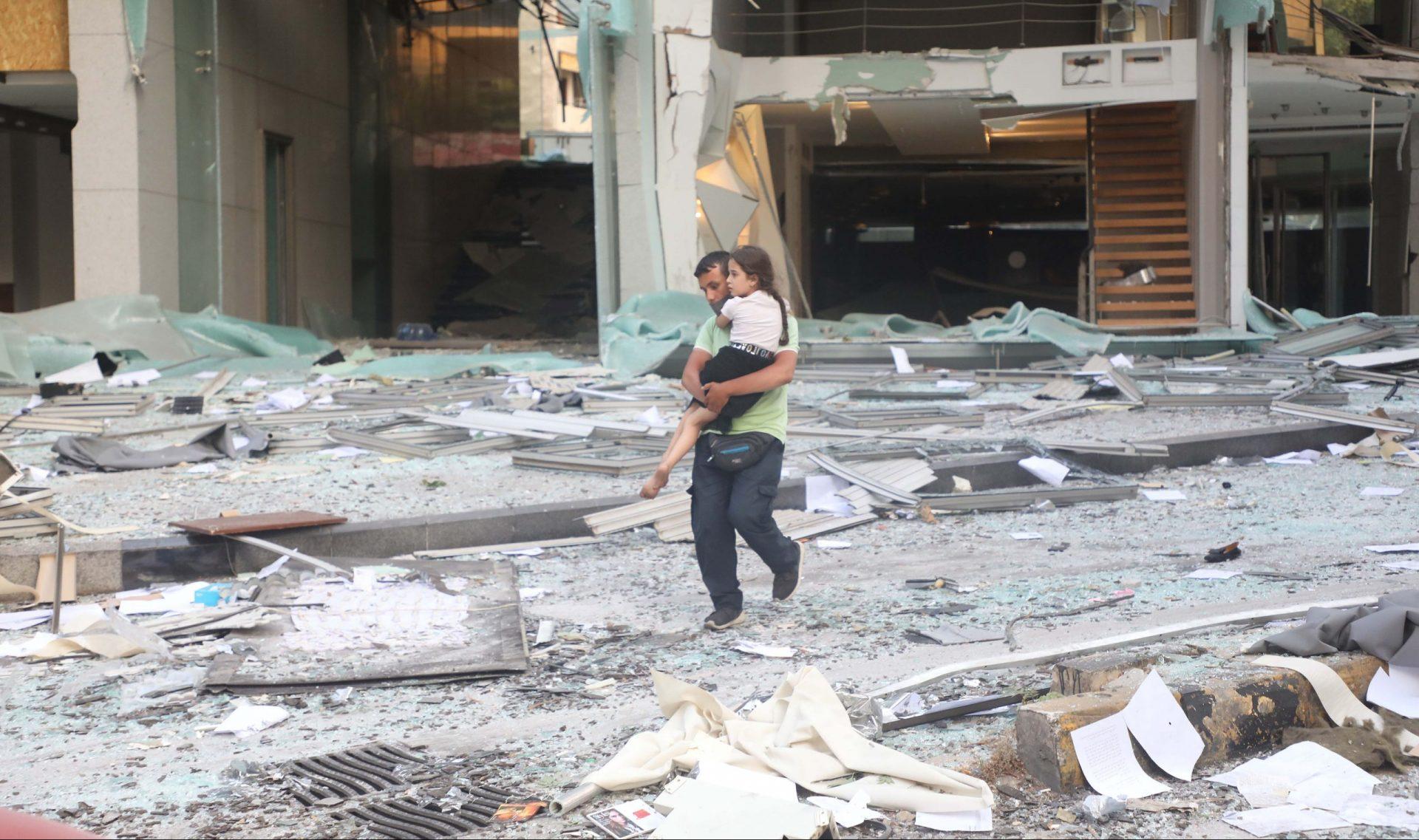 En mand bærer en pige forbi ruinerne efter eksplosionen d. 4. august i Beirut. FOTO: Scanpix